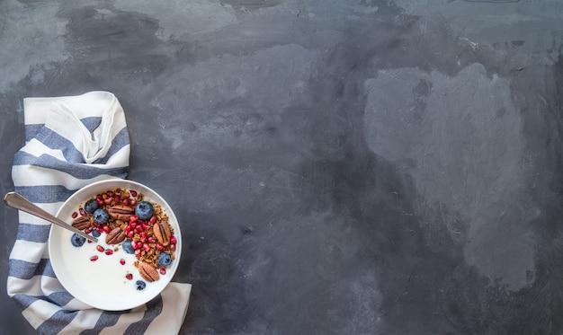 Domowe musli z musli z pestkami granatu, jagodami, orzechami pekan i jogurtem
