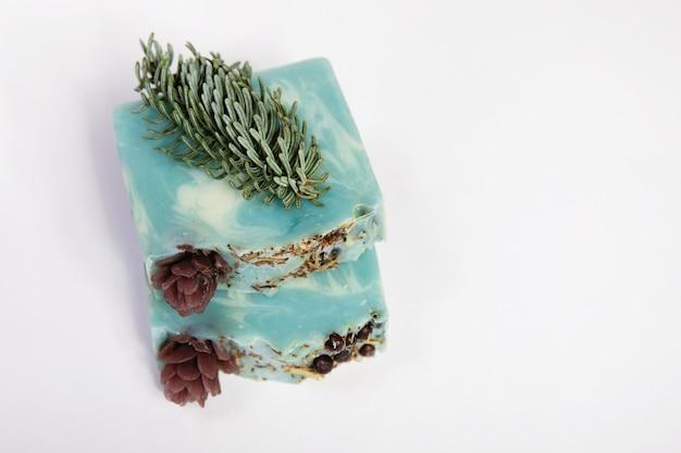 Domowe mydło ręcznie robione. aromat iglasty, świerkowa gałązka i stożek, sznurek jutowy. mały biznes, produkty ekologiczne, naturalne składniki. widok z góry.
