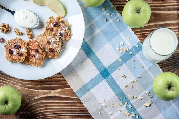 Domowe naleśniki owsiane z jogurtem wegańskim, rodzynkami i orzechami włoskimi na drewnianym stole z niebieskim materiałem w pudełku.