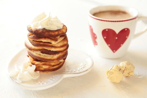 Domowe naleśniki z filiżanką kawy śniadaniowej z sercem na białym tle