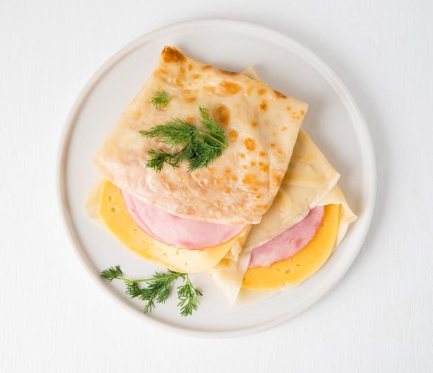 Domowe naleśniki z szynką i serem na białej powierzchni, maslenitsa, widok z góry