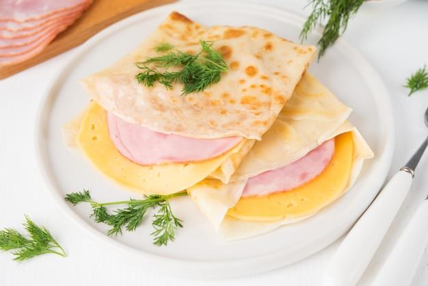 Domowe naleśniki z szynką i serem na białej powierzchni, maslenitsa