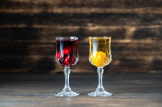 Domowe nalewki z czerwonej wiśni i żółtej śliwki wiśniowej w kryształowych kieliszkach do wina na drewniane tła, ukraina, z bliska. koncepcja napojów alkoholowych jagodowych