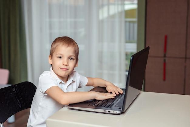Domowe nauczanie na odległość dzieci podczas kwarantanny. szczęśliwy chłopca w białym polo odrabiania lekcji za pomocą laptopa siedząc w domu w kuchni