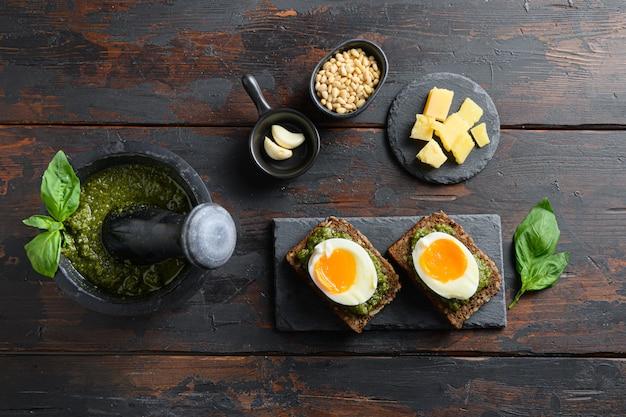 Domowe pesto alla genovese w czarnym moździerzu ze składnikami i gotowanymi jajkami