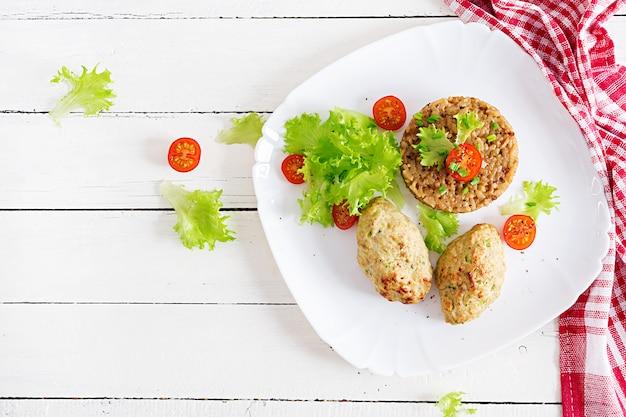 Domowe pieczone kotlety z ryżem na stole w stylu rustykalnym. zdrowe jedzenie. widok z góry