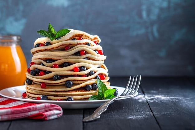 Domowe pieczone naleśniki ze świeżymi jagodami i słoik dżemu na pyszne śniadanie