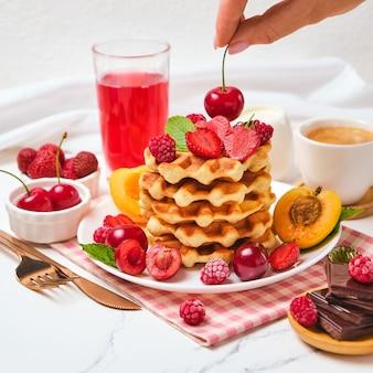 Domowe pieczone tradycyjne gofry belgijskie z owocami jagodowymi i filiżanką kawy, selektywne skupienie. kobieca ręka kładzie wiśnie na gofry