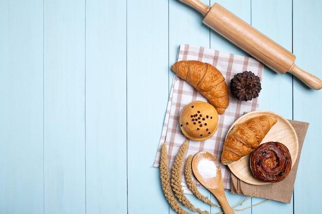Domowe pieczywo lub bułka, rogalik i wałek do ciasta, trzepaczka, mąka na niebieskim drewnie