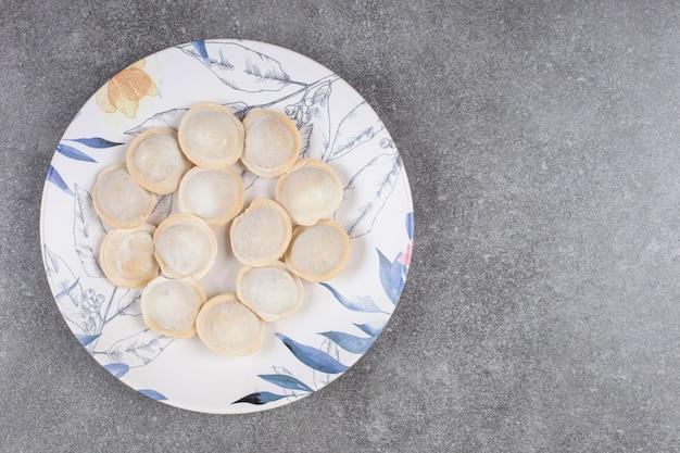Domowe pierogi gotowane na kolorowym talerzu