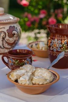 Domowe pierogi w glinianych etnicznych ukraińskich potrawach na stole w letnim ogrodzie.