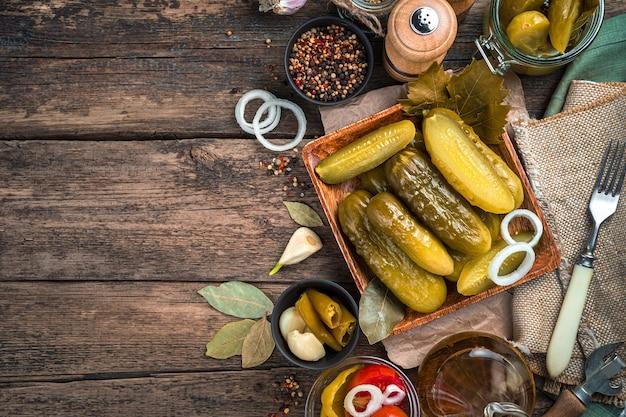 Domowe pikle na lnianej serwetce na drewnianym tle. widok z góry. pojęcie tła kulinarnego.