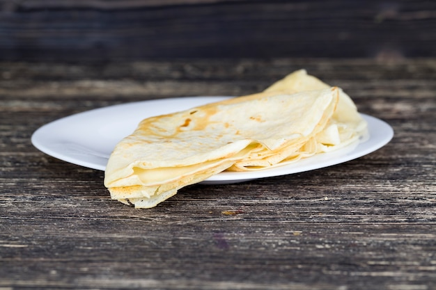 Domowe placki pszenne z masłem na szklanym talerzu