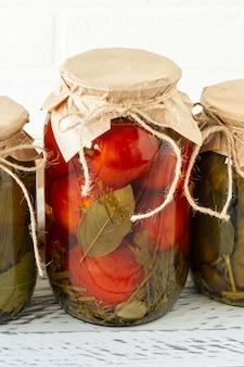 Domowe pomidory i ogórki konserwy w szklanym słoju na drewniane tła.