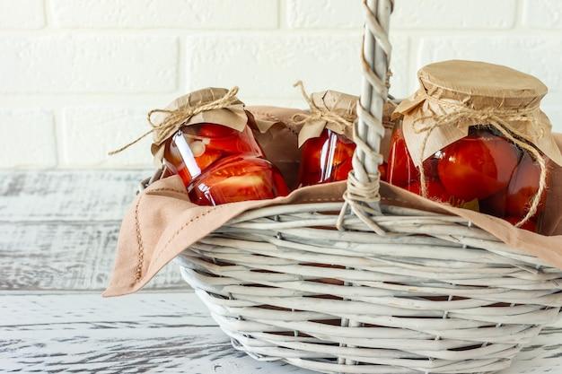 Domowe pomidory przetwory w szklanych słoikach w białym wiklinowym koszu na drewniane tła.