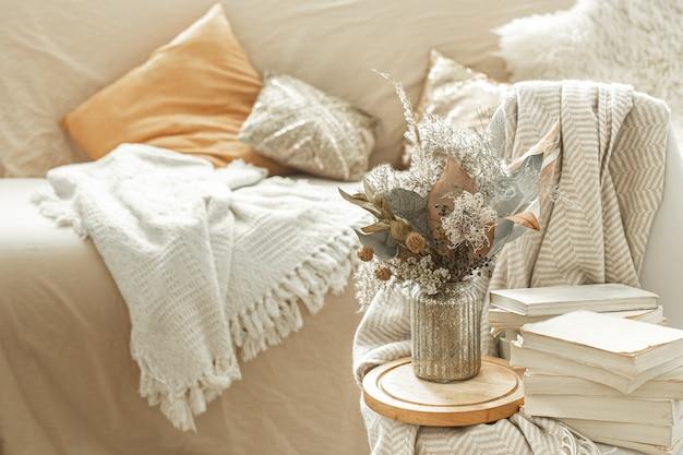 Domowe przytulne wnętrze pokoju z książkami i suszonymi kwiatami w wazonie.