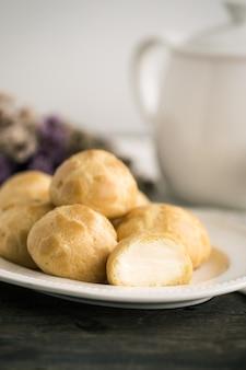 Domowe ptysie śmietankowe lub choux cream lub eclairs podawane z herbatą w białym garnuszku lub filiżance kawy