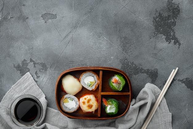 Domowe pudełko bento sushi z zestawem rolek sushi, na szarym tle kamienia, płaski widok z góry, z copyspace i miejscem na tekst