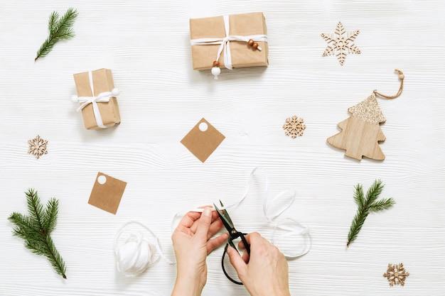 Domowe pudełko upominkowe, pudełko na prezent świąteczny zawinięte w papier pakowy, kobieca wstążka do cięcia ręcznego