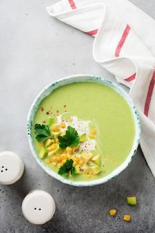Domowe puree z delikatnej zupy z awokado i kukurydzy ze śmietaną w rustykalnym talerzu ceramicznym na szarej betonowej powierzchni. selektywna ostrość. widok z góry.