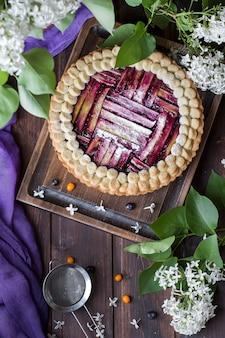 Domowe pyszne ciasto rabarbarowe z jagodami na ciemnym tle
