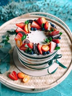 Domowe pyszne i soczyste ciasto ozdobione żywymi truskawkami i jagodami na niebieskim tle