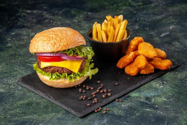 Domowe pyszne kanapki frytki nuggetsy z kurczaka na czarnej desce do krojenia frytki pieprz na ciemnoszarej rozmytej powierzchni