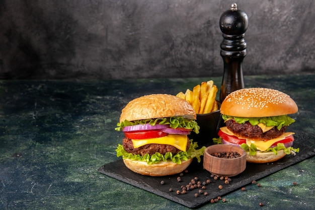 Domowe pyszne kanapki na czarnej desce do krojenia frytki pieprz na ciemnoszarej rozmytej powierzchni
