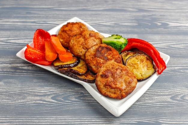 Domowe pyszne kotlety z pieczonymi warzywami.