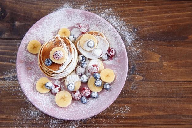 Domowe pyszne naleśniki ze świeżymi jagodami posypane cukrem pudrem na fioletowym talerzu. smaczne i zdrowe śniadanie naleśników z malinami i jagodami. widok z góry.