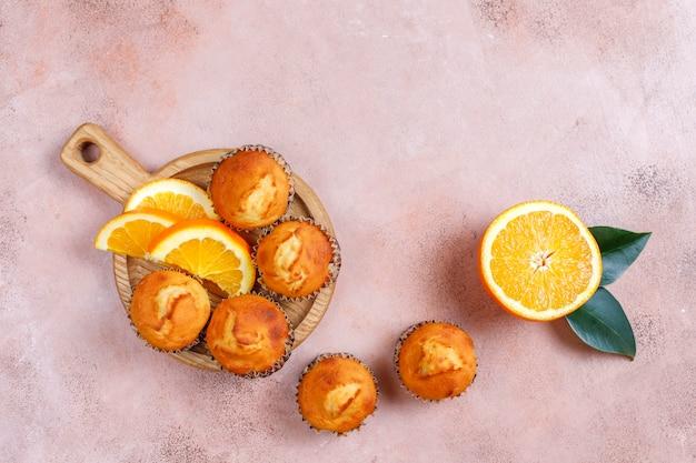 Domowe pyszne pomarańczowe babeczki ze świeżymi pomarańczami.