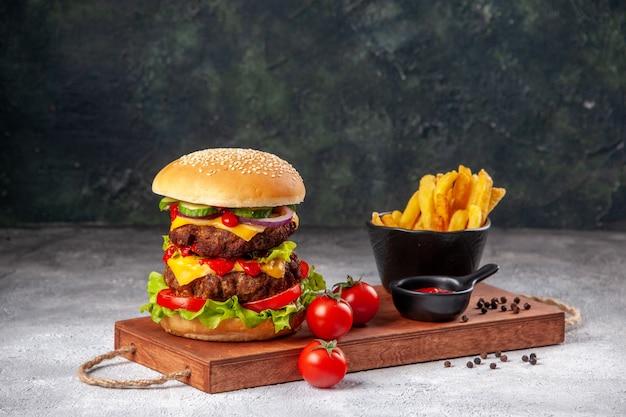 Domowe pyszne pomidory kanapkowe ketchup frytki z papryką na desce do krojenia na zamazanej powierzchni