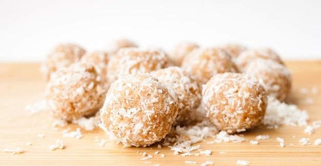 Domowe ręcznie robione słodkie cukierki w wiórkach kokosowych na naturalnym bambusowym drewnie. pojęcie zdrowego stylu życia. ścieśniać. selektywna nieostrość. miejsce na kopię tekstu.