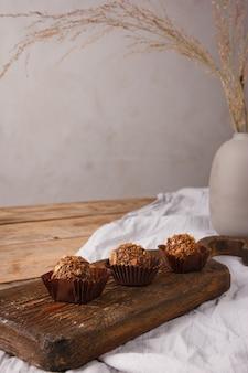 Domowe ręcznie robione słodycze i cukierki na rustykalnym drewnianym stole z szarym obrusem. domowe zdrowe słodycze, pyszny deser, naturalne słodycze i cukierki.