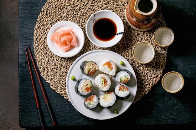 Domowe rolki sushi z łososiem, japońskim omletem, avacado, imbirem, sosem sojowym z pałeczkami na słomianej serwetce na czarnym drewnianym stole. ceramiczny zestaw do sake. widok z góry, układ płaski. kolacja w stylu japońskim
