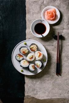 Domowe rolki sushi z łososiem, japońskim omletem, avacado, imbirem, wasabi i sosem sojowym z pałeczkami na szarym papierze na czarnym drewnianym tle. widok z góry, układ płaski. kolacja w stylu japońskim