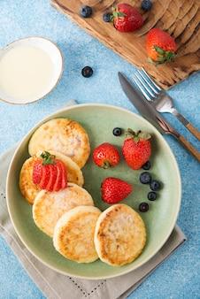 Domowe serniki smażone ze skondensowanym mlekiem i jagodami, widok z góry