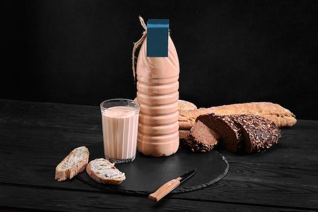 Domowe sfermentowane mleko pieczone w przezroczystej misce na starym ciemnym tle. rustykalny. produkty mleczne. obraz tła, miejsce na kopię.