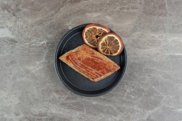 Domowe smaczne ciasto na talerzu z plastrami pomarańczy