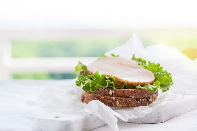 Domowe smaczne kanapki z sałatą i szynką na pokładzie cięcia