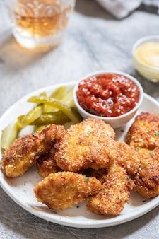Domowe smażone chrupiące nuggetsy z kurczaka z keczupem i piklami