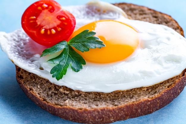 Domowe, smażone jajka z kurczaka z bułką, świeżą pietruszką i pomidorkami cherry na zdrowe śniadanie. żywność białkowa. kanapka jajka