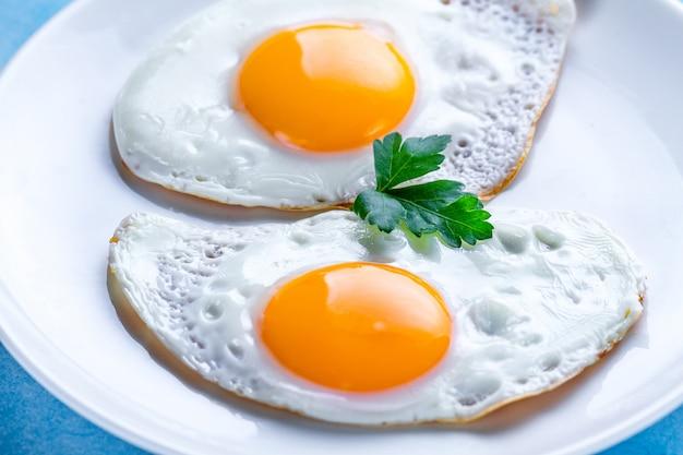 Domowe, smażone jajka z kurczaka ze świeżą pietruszką z bliska na śniadanie. żywność białkowa.