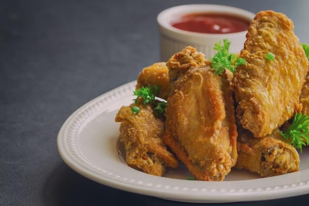 Domowe smażone skrzydełka z kurczaka na białym talerzu serwowane z grilla zanurzenie sos.