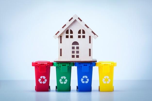 Domowe śmieci. model domu na koszach na śmieci na szarej powierzchni.