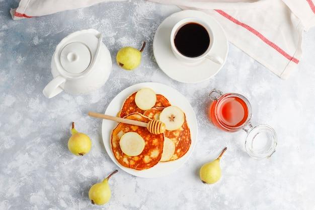 Domowe śniadanie: amerykańskie naleśniki podawane z gruszkami i miodem z filiżanką herbaty na betonie. widok z góry i kopiowanie
