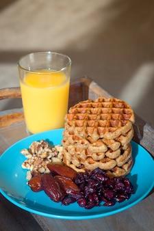 Domowe śniadanie - wafle owsiane z suszonymi owocami, orzechami i sokiem.