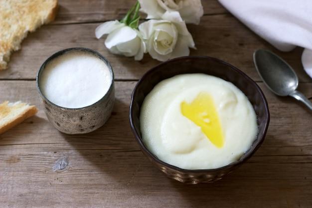 Domowe śniadanie z kaszy manny, kawy z mlekiem i tostów na drewnianej powierzchni. styl rustykalny.