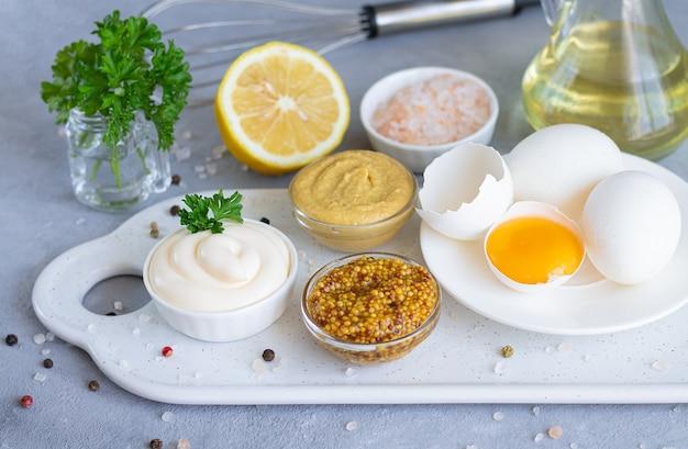 Domowe sosy: majonez, musztarda i sos musztardowy dijon ze składnikami do ich gotowania