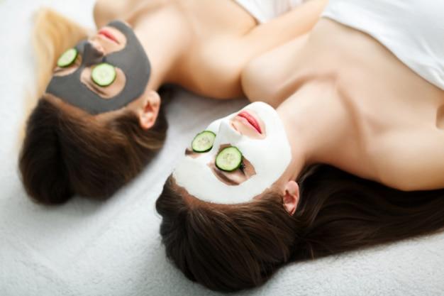 Domowe spa. dwie kobiety trzymające kawałki ogórka na twarzach leżące na łóżku.